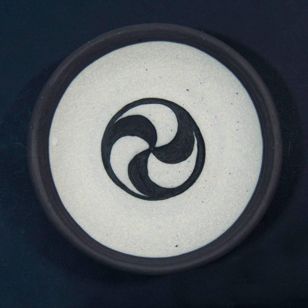 Plato negro sin esmalte con decoración de grabados rupestres. Petroglifo. Hecho a mano en Galicia