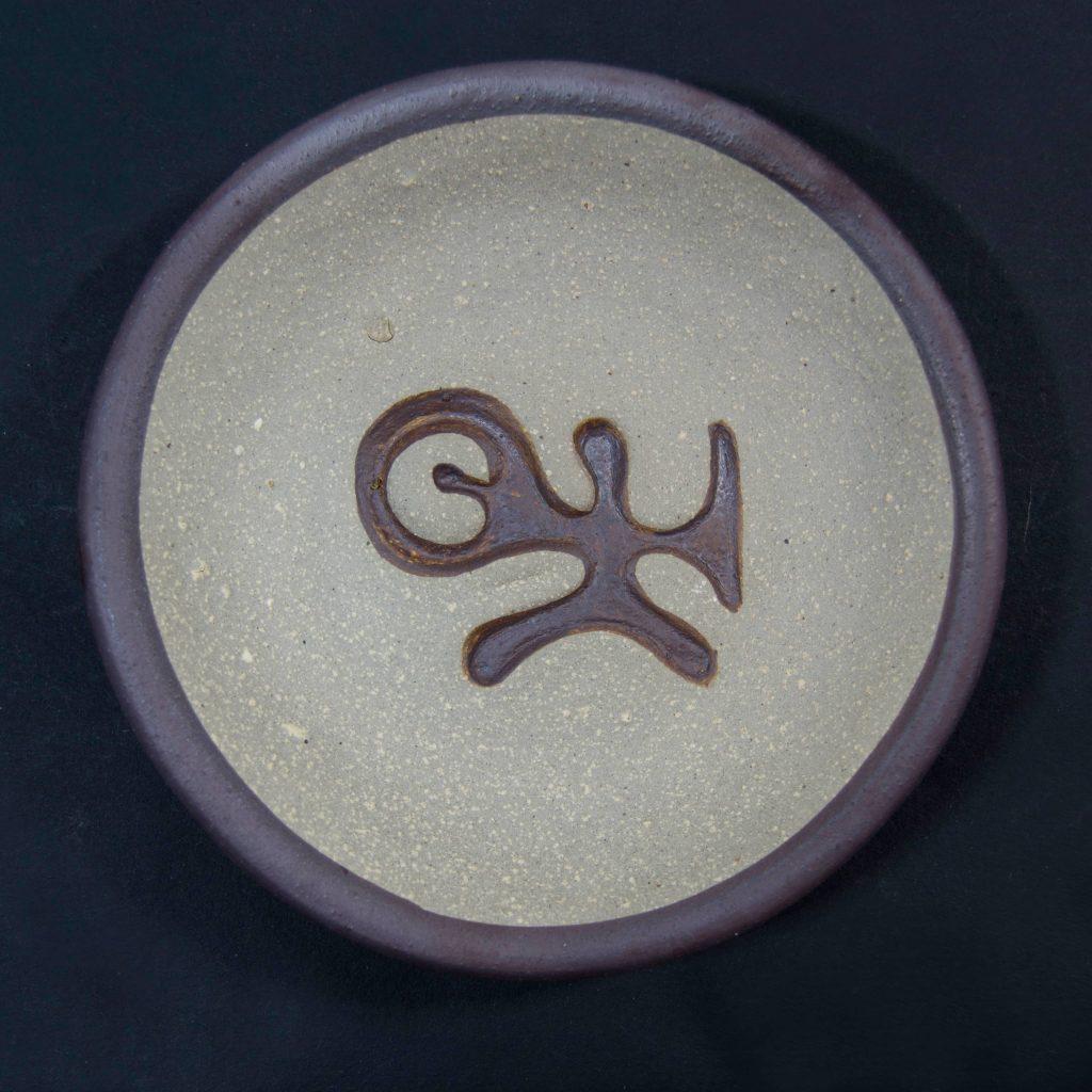 Plato marrón sin esmalte con decoración de grabados rupestres. Petroglifo, motivo pedra das ferraduras. Ubicado en Cotobade, Pontevedra. Hecho a mano en Galicia
