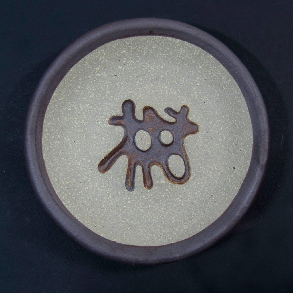 Plato marrón sin esmalte con decoración de grabados rupestres. Petroglifo, motivo pedra dos chetos. Ubicado en Oia, Pontevedra. Hecho a mano en Galicia
